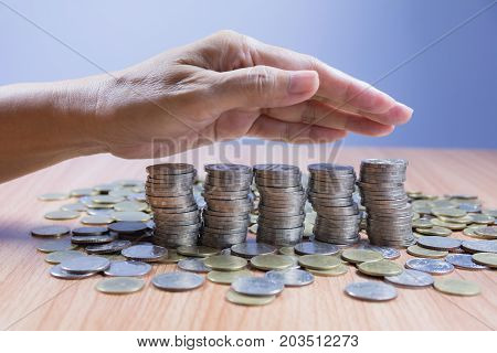 stack coins with hand of businessman cover stack coins. Financial and saving concept.