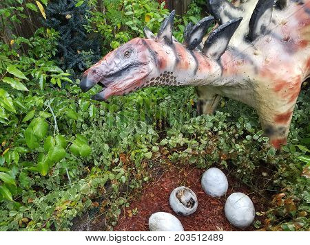 a baby dinosaur hatching from an egg on the ground with the mother