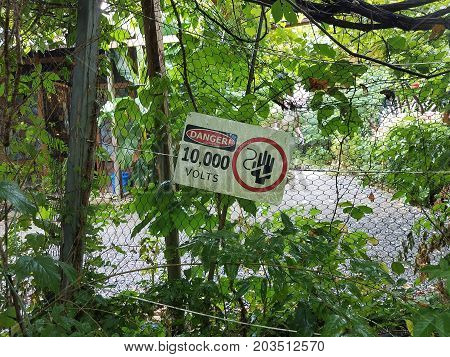 a danger 10, 000 volts sign on metal chain link fence