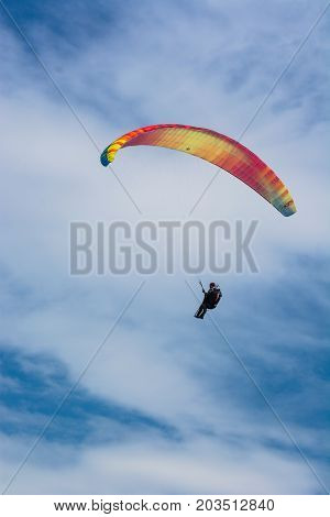 Paraglider Flies In The Blue Summer Sky