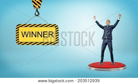 A happy businessman stands on a red pushbutton near a construction sign reading Winner. Business and competitions. Getting on top. Lottery and income.
