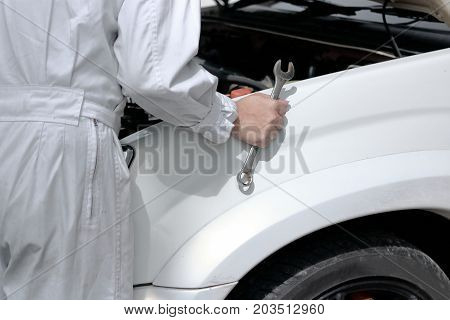Side view of automotive mechanic in uniform with wrench diagnosing engine under hood of car at the repair garage.