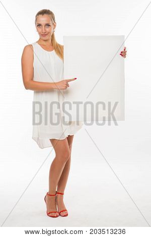 Young playful woman portrait of a confident businesswoman showing presentation, pointing placard gray background. Ideal for banners, registration forms, presentation, landings, presenting concept.