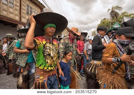 June 24 2017 Cotacachi Ecuador: indigenous kichwa people wearing chaps dancing in the crowd at the Inti Raymi parade at summer solstice