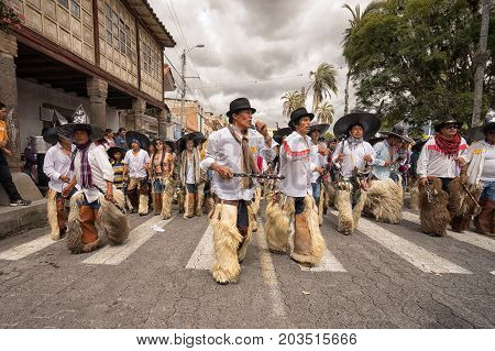 June 24 2017 Cotacachi Ecuador: indigenous kichwa men wearing chaps dancing at the Inti Raymi parade at summer solstice