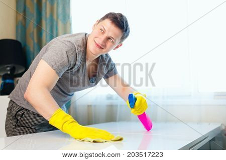 The Young Man Rubs The Dust On The Table.a House Cleaner Cleans Up Dust.boy Smiling And Doing House