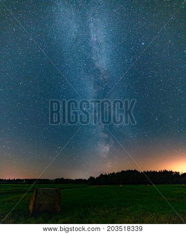 Blue dark night sky with many stars above field of trees. Milkyway cosmos background