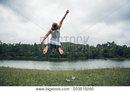 Asian women travel relax in the holiday. Jump on a green pasture.