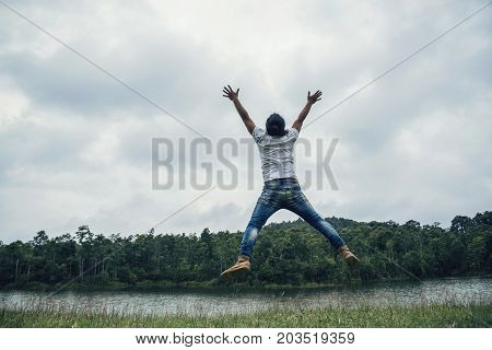 Asian man travel relax in the holiday. Jump on a green pasture.