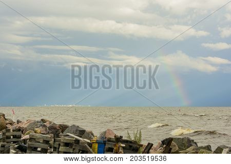 garbage on the shore of the reservoir river sea ocean on the horizon in the sunlight city and rainbow