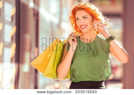 Woman holding many shopping bags in fashion boutique.
