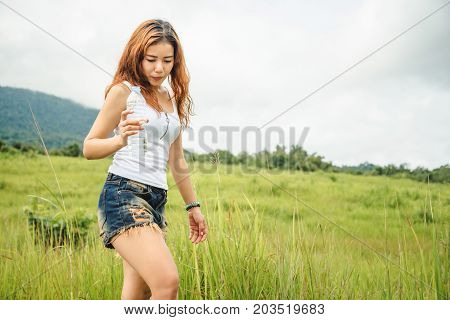 Asian women travel relax in the holiday. Drink Water on a green pasture.