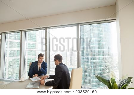 Financial analyst telling about prospects of project to investor during meeting. Two businessmen working with business documents at desk in modern office building with skyscrapers outside the window