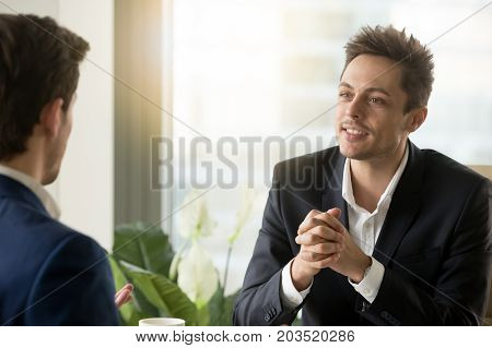 Portrait of handsome businessman getting interesting offer from business partner sitting opposite. Millennial employee in business suit talking with colleague, listening coworkers personal opinion
