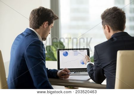 Businesspeople sitting at desk discussing financial indicators on laptop pc screen. Entrepreneur explaining to partner company profit perspectives according to economic forecast. Back view image