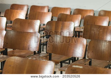 School classroom with old desks chair wood in high school thailand vintage tone education concept