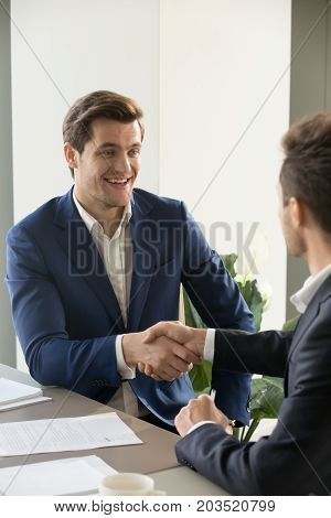 Successful businessman congratulating partner with great deal, offering partnership, introducing himself during important business negotiation. Director welcoming with handshaking new company employee