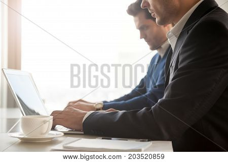 Two office workers in business suits using laptops at desk. Businessmen typing on ps while working together on project in cafe. Financial analysts or brokers monitoring stock indices. Close up image
