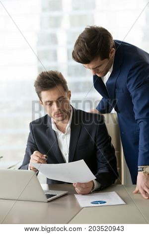 Manager leaning over employee sitting at desk with laptop and showing business document. Office worker explaining details of project, telling about features in plan, presenting work result to boss