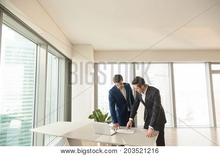 Realtor showing apartments or home plan to client while standing together near desk in office. Successful architects planning new project, discussing building drawings, working on construction budget