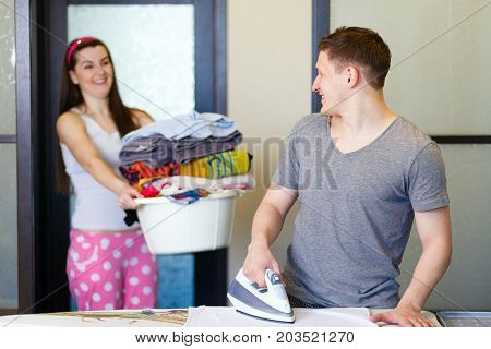 Man Husband Ironing At Home Helping His Wife