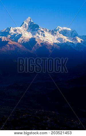 Snow capped top of Machapuchare Fishtail Himalayan mountain lighted by early morning dawn sunlight with dark valley below Sarangkot Nepal poster