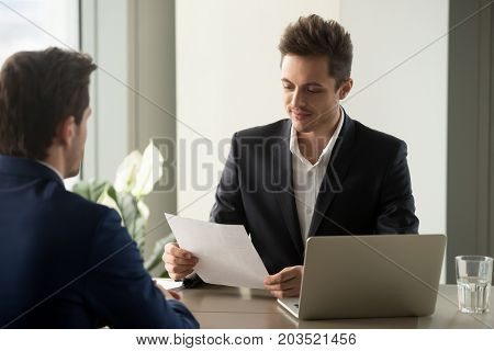 Attractive millennial businessman carefully reading text of contract, examining conditions of companies partnership while meeting with business partner in office. HR manager studying candidate resume
