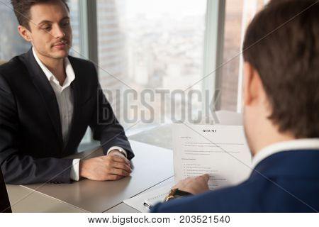 Back view of hiring manager pointing on clauses in resume and asking job applicant questions. Employer conducting interview with candidate, specifying work experience. Close up image, focus on resume