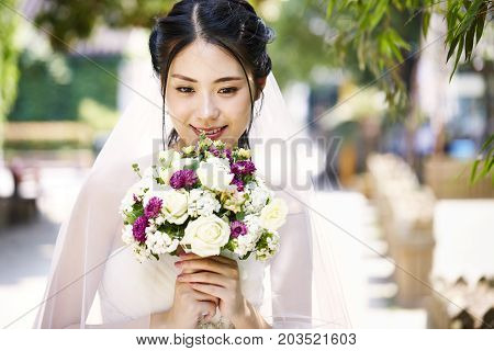 beautiful and happy young asian bride wearing bridal veil holding a bunch of flower