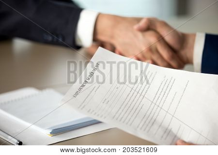 Close up photo of employment agreement document in hand of hiring manager shaking hand of job candidate. Employer offering work contract to applicant, successful interview, positive hiring decision