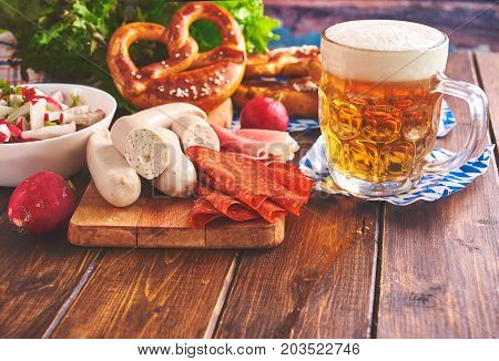 Traditional munich Oktoberfest food including white sausages, pretzels and beer. Toning.