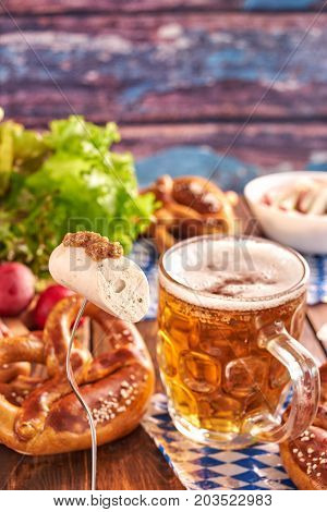 Traditional munich white sausage on fork, mug of beer and pretzels on wooden table for Oktoberfest. Vertical shot.