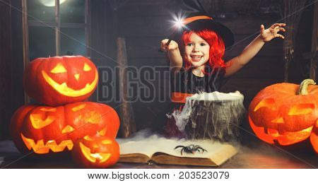 Halloween. little witch child cooking potion in the cauldron with pumpkin and spell book