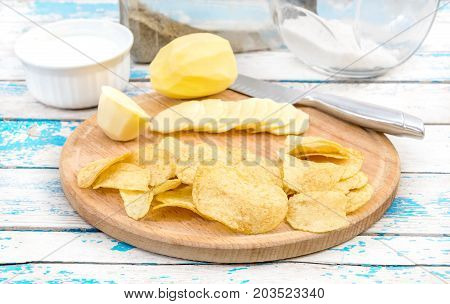 Cutting board with raw potato potato chips knife and spices on old wooden table. Preparing potato chips.
