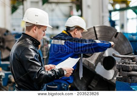 A Young Successful Engineer With A Drawing In His Hands Controls The Work Of His Subordinate In The
