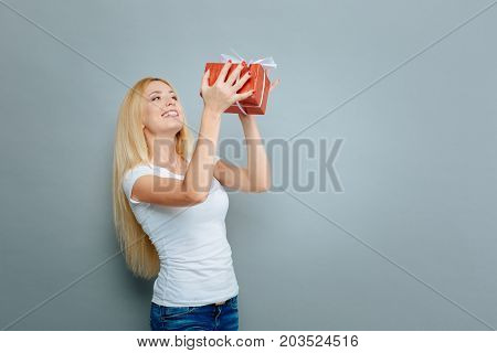 I am happy. Happy female person standing in semi position and keeping smile on her face while looking forward, isolated on grey