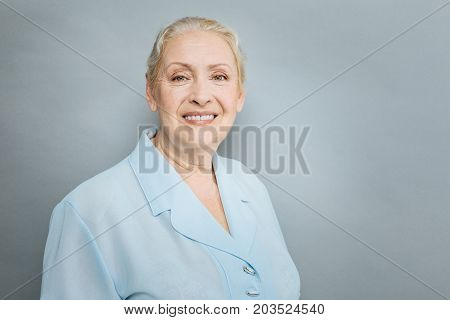 Happy old age. Portrait of beautiful female that keeping smile on her face and feeling happiness while standing isolated on grey