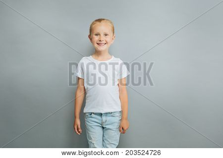 Happy childhood. Delighted blonde girl keeping smile on face and looking forward while standing isolated on gray background