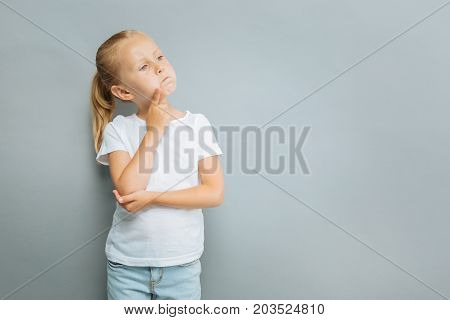 Have some thoughts. Beautiful kid turning head and touching chin while looking sideways, isolated on grey