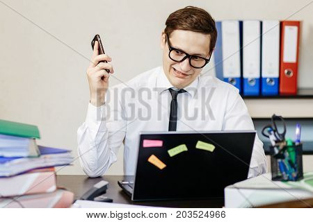 A Young Handsome Man Is Sitting In The Office At His Workplace In Front Of A Laptop And Hears A Repr