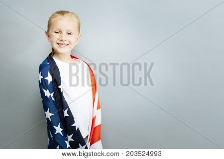 Patriotic mood. Attractive kid expressing positivity and looking forward while standing over grey background