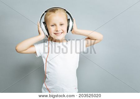 I am music lover. Amazing girl keeping smile on her face and raising hands while posing on camera