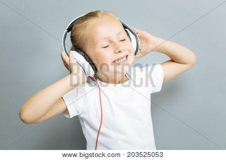 Love music. Beautiful child closing eyes and keeping smile on her face while expressing positivity