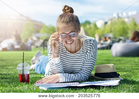 Outdoor Image Of Young Caucasian Female Spending Time In Open Air, Reading Materials For Studies Wit