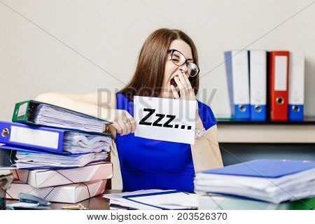 Young Beautiful Girl In Glasses And Blue Dress Yawns At Her Workplace In The Office