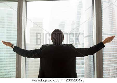Successful businessman in dress suit standing in office in front of sunshine lit window with arms wide open. Welcoming new successful deals, business opportunities and bright future concept. Back view