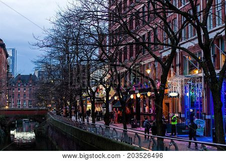MANCHESTER UNITED KINGDOM - 5 March 2016: Evening view of a lit up street and canal in the city of Manchester in the north of England.