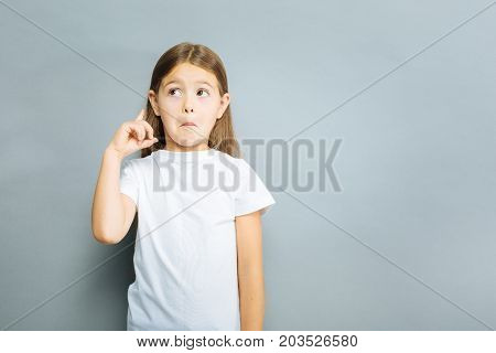 Making faces. Serious child pressing lips and pointing upwards while standing over grey background