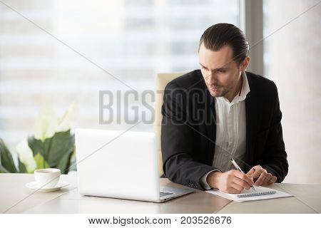 Handsome young businessman in nice suit sitting in the office and looking at the laptop screen, he is writing down important notes. Business plan, project planning or stock market investment concept.
