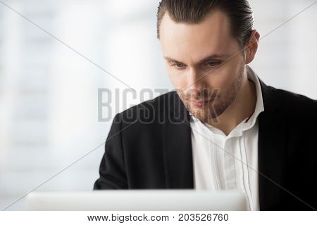 Smart young businessman in dress suit sitting in office, looking at laptop screen with thoughtful expression, contemplating an important project or looking for information concept. Close up portrait